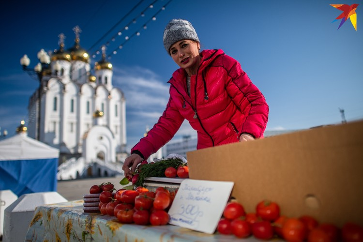 Женщина торгует помидорами.