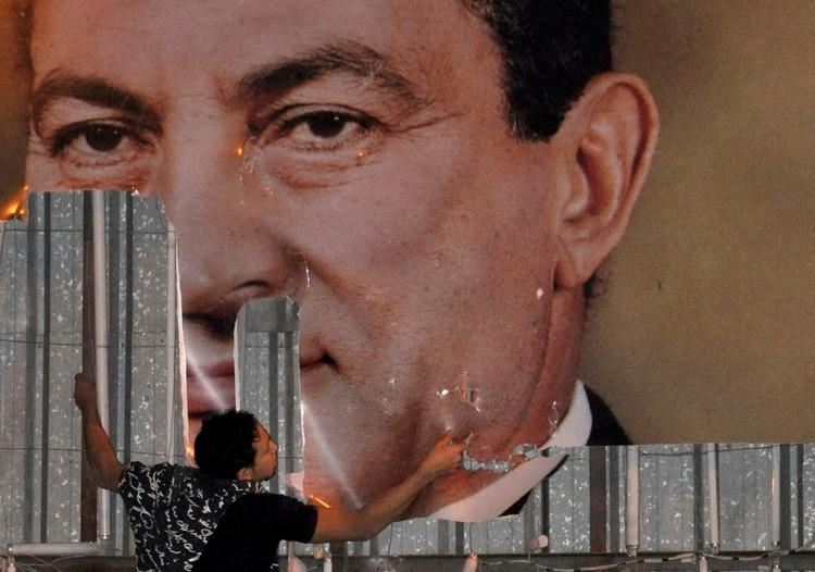 Участник протестов срывает портрет Мубарака с президентского дворца в Александрии, 2011 год.