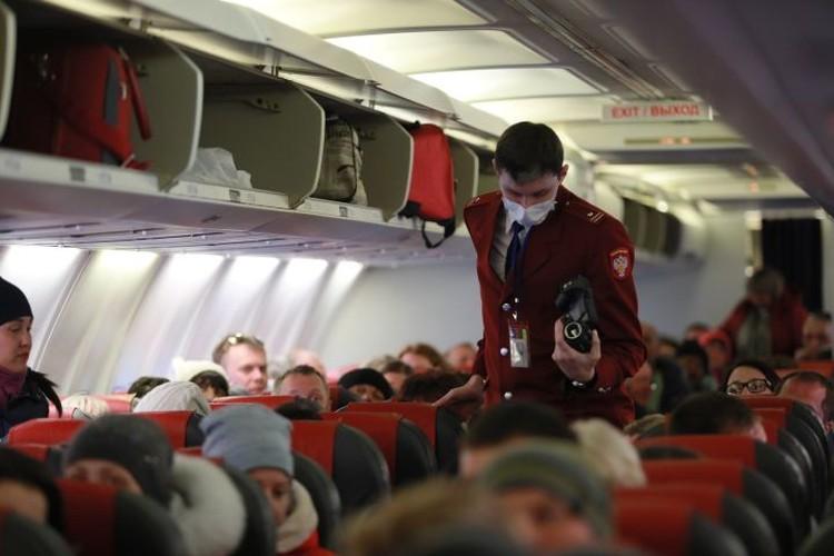 Сотрудник Роспотребнадзора проверяет тепловизором пассажиров прибывшего самолета в связи с эпидемией коронавируса.