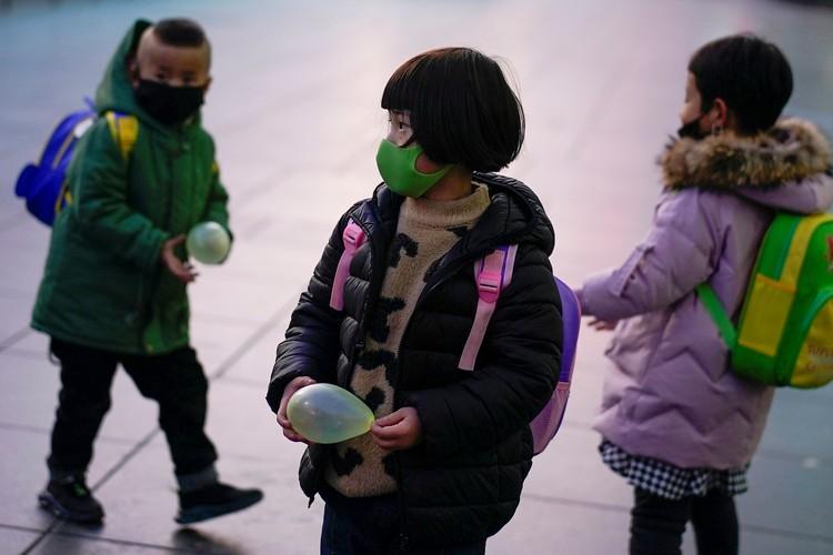Дети в медицинских масках на улицах Шанхая.