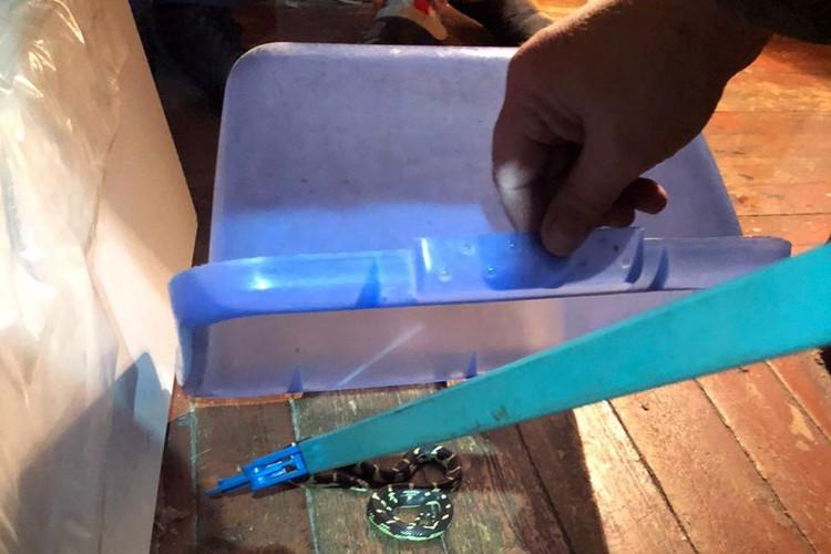 Спасатели уверенно, как настоящие змееловы с помощью металлического прута поймали и переместили змею в пластмассовый контейнер