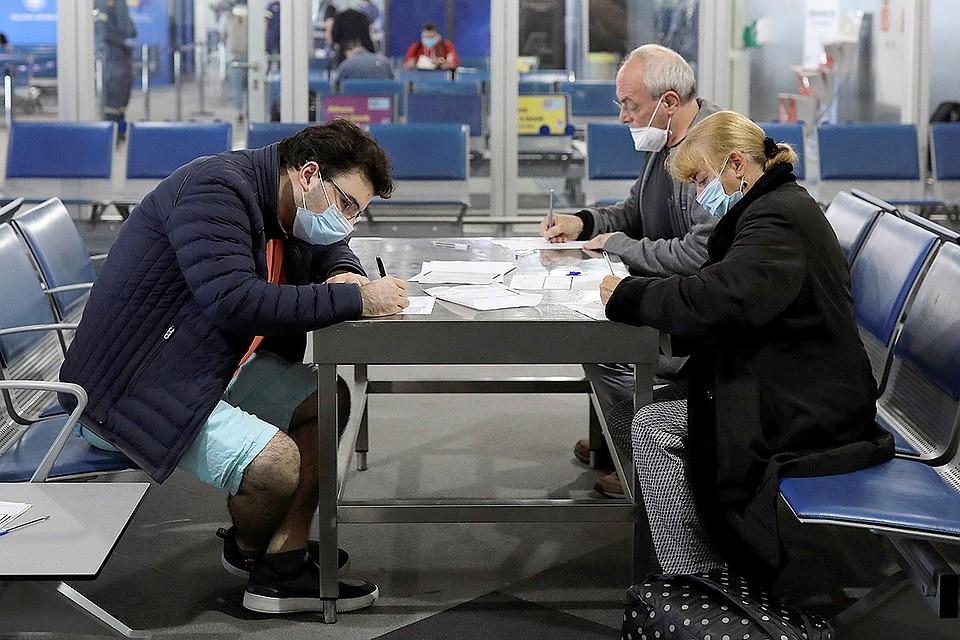 """Пассажиры заполняют """"карантинные"""" бланки в аэропорту Афин, где возобновили часть рейсов. Фото: REUTERS"""
