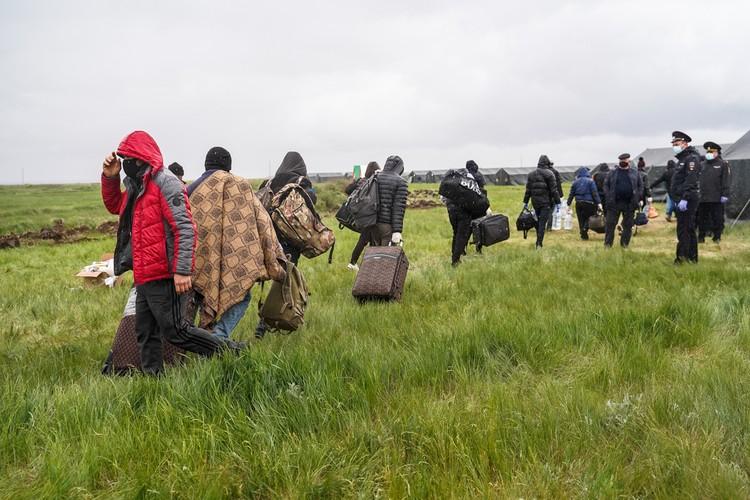 Полиция уводит из под дождя тех, кто ждет автобуса до Узбекистана