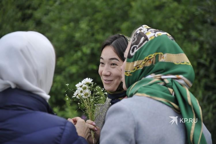 Ксения ЛИ вместе с другими послушницами собирает полевые цветы.