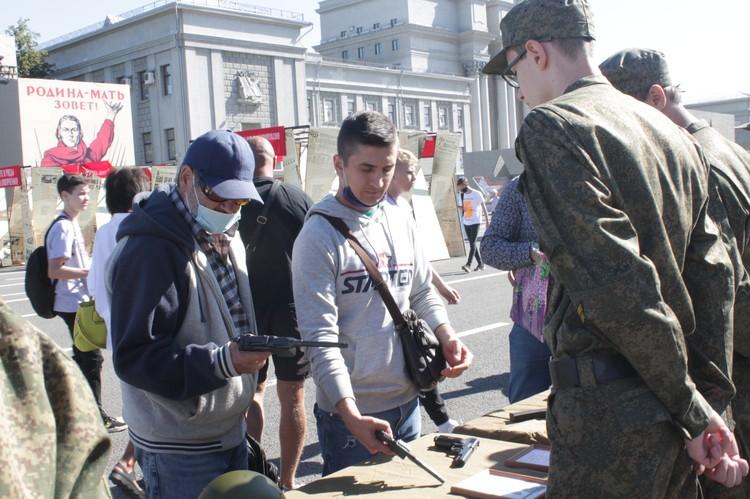 Мужчины сразу останавливаются около столиков с оружием