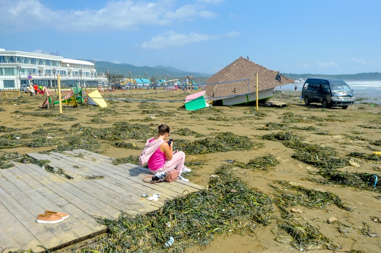 Работники пляжа собирают уцелевшее