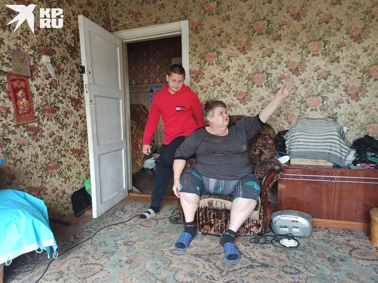 Бабушка показывает на стены и потолок. Она просит чиновников дать им соцжилье.