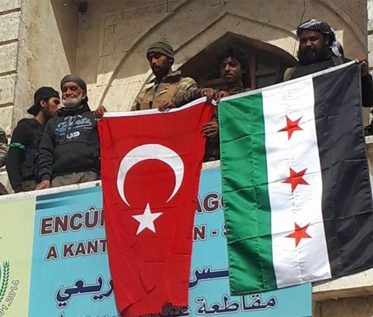 Бойцы «Сирийской национальной армии» демонстрируют турецкий флаг после захвата города на севере Сирии, 2018 г.
