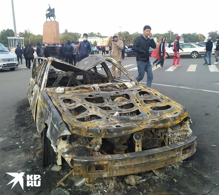 Сожженный в ходе беспорядков автомобиль в центре города.
