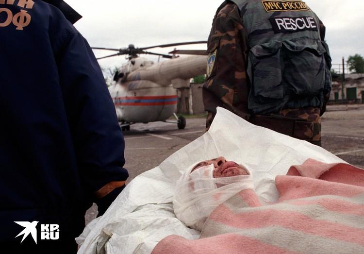 Спасатели несут к вертолету раненого жителя Грозного для эвакуации в госпиталь. Грозный, февраль 1995