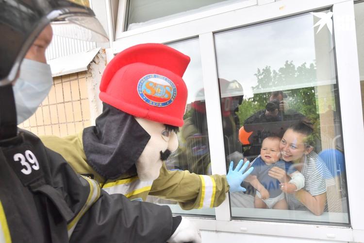 В день защиты детей спасатели МЧС поздравляют детей больных коронавирусом в детской больнице Москвы через стекло окна третьего этажа