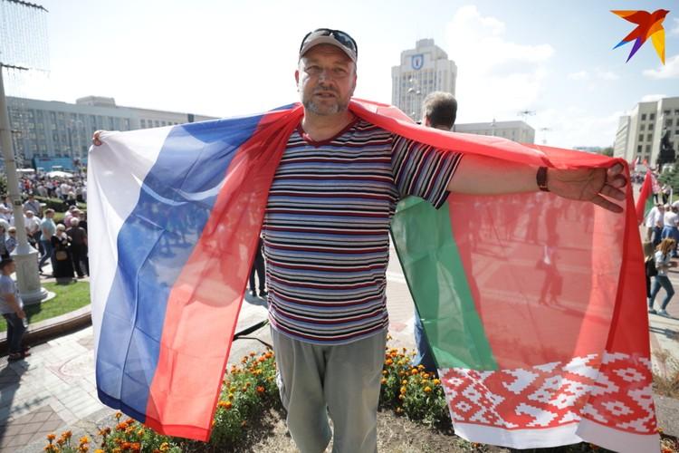 Мужчина с флагами на митинге в поддержку Александра Лукашенко. Минск, площадь Независимости, 16 августа 2020 года.