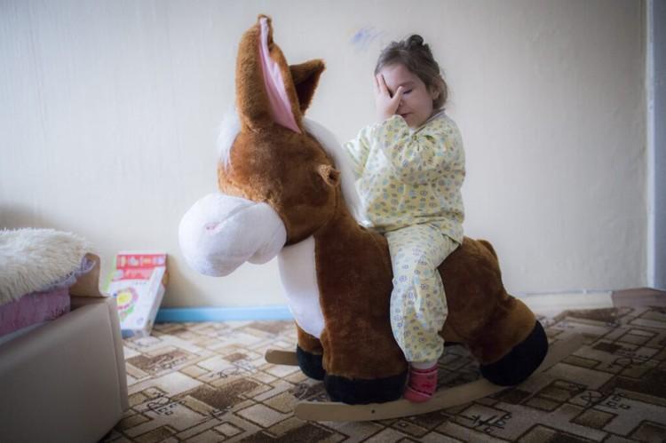 Алина качается на игрушечном ослике. Фото: Ольга Карпушина для свет.дети
