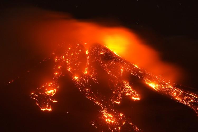 Лава течет по склонам вулкана.