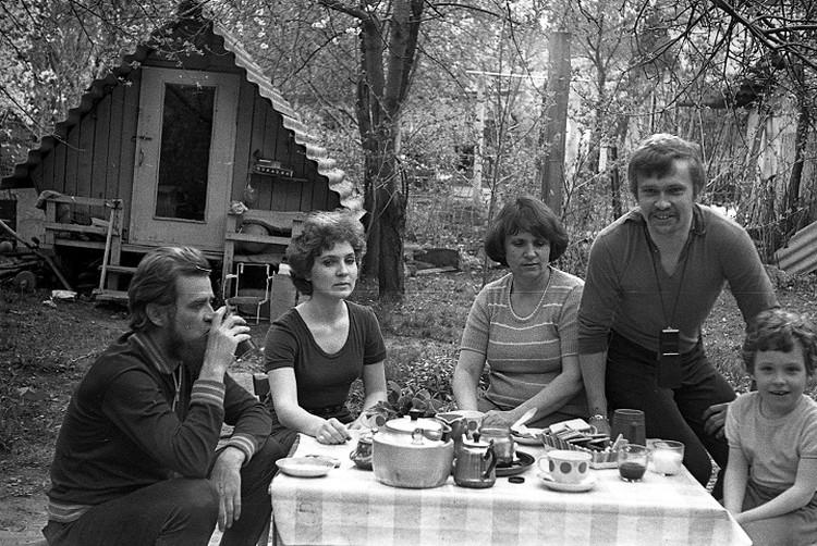 Семья в саду, за ужином. Летний домик на заднем плане тоже построил отец.
