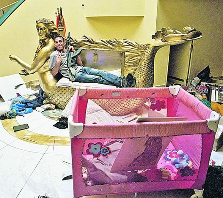 Какое символичное фото! Повстанец разлегся на диванчике в виде золоченой русалки  с лицом Аиши Каддафи - дочери полковника. Как тут не вспомнить,  что операция по захвату Триполи как раз носила кодовое название «Русалка».