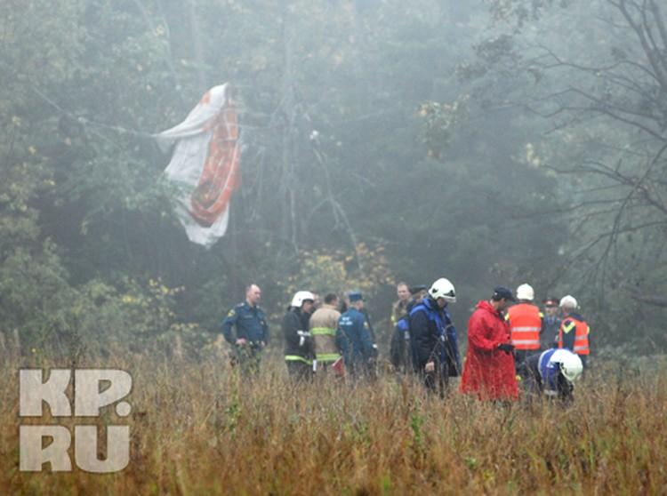 Спасатели и МЧС работают на месте крушения. На заднем фоне - тормозной парашют МиГа.