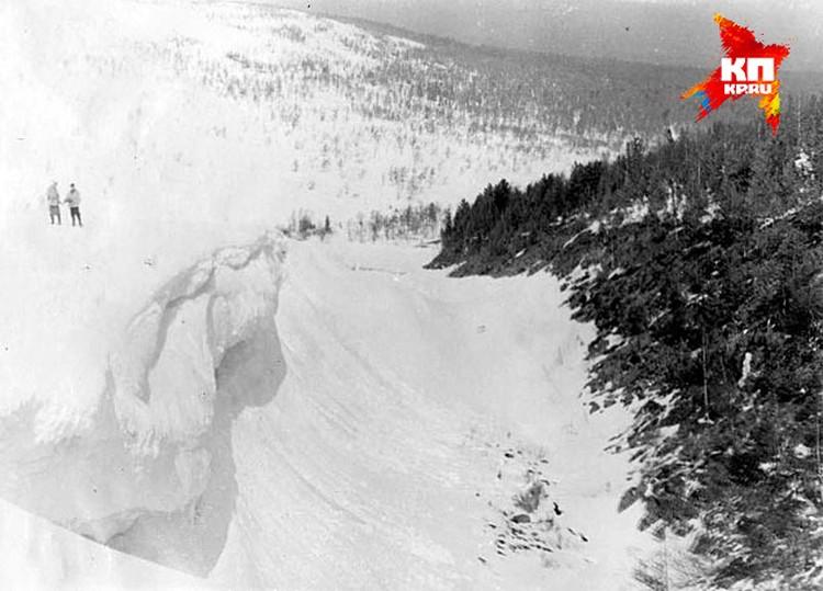 Если предположить, что туристы устроили настил в овраге примерно вот под таким козырьком, а потом подрыли пещеру, то их могло подавить обрушившимся снегом. Отсюда и переломы ребер, и травма черепа