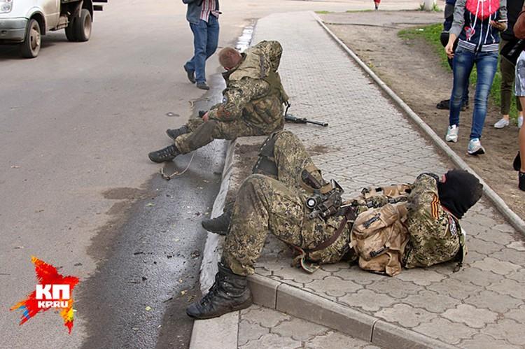 Бойцы самообороны Славянска, только вырвавшиеся из боя, валятся от усталости на тротуар