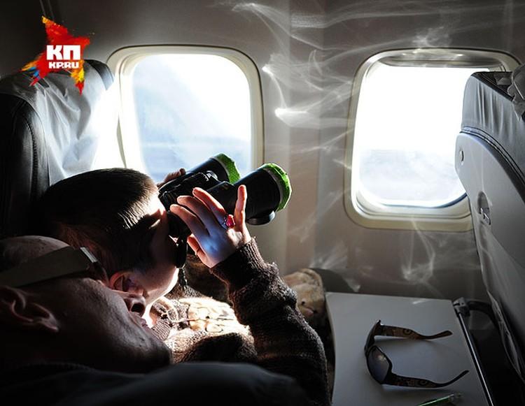 Пассажиры наблюдали затмение через самые разнообразные приспособления.